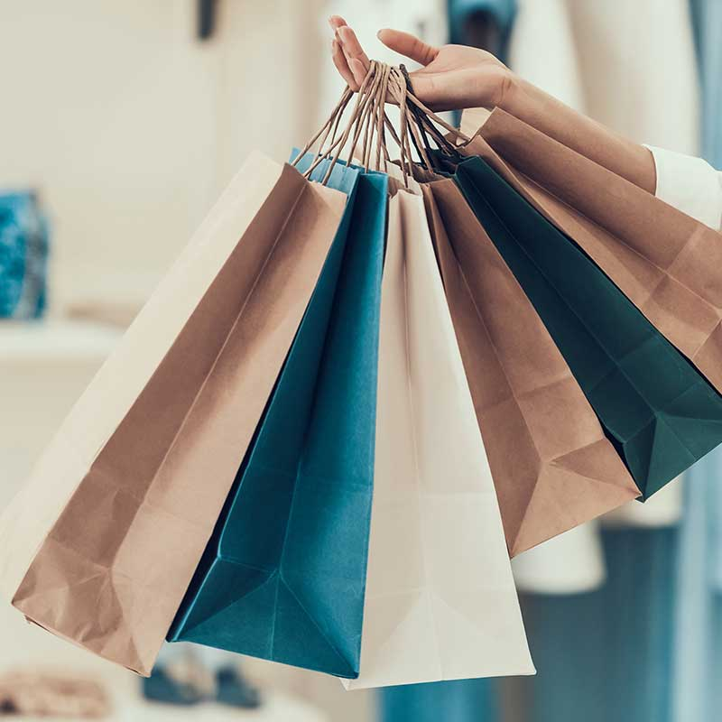 Hand holding multiple shopping bags