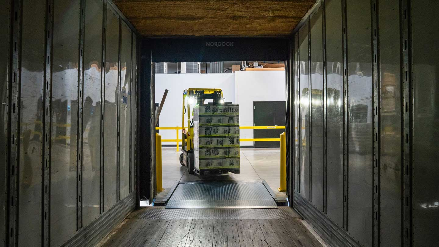Forklift loading a pallet of supplies onto a semi-truck